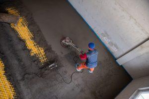 Ein Arbeiter trägt Estrich auf. Was es zu beachten gibt erfahren Sie auf Tipp zum Bau.