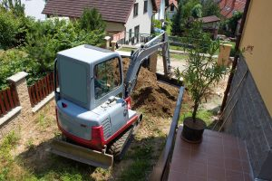 Ein Bagger öffnet das Erdreich im Garten.