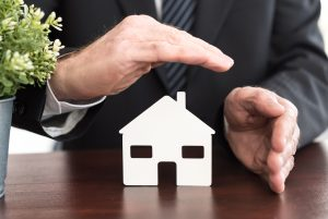 Verteter beschützt Haus mit Händen