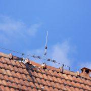 Blitzdraht als Blitzableiter auf einem Dach mit Tonziegeln.