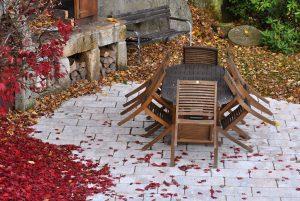 Gartentisch und -stühle gehören zur Gartenmöbel-Garnitur.