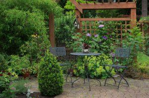 Gemütliche kleine Hinterhofterrasse mit Tisch und Stuhl im Garten.