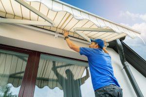 Arbeiter installiert eine Markise an der Hauswand über ein Terrassenfenster.