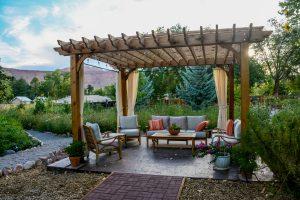 Innenhof mit Gartenmöbel unter einer Pergola.